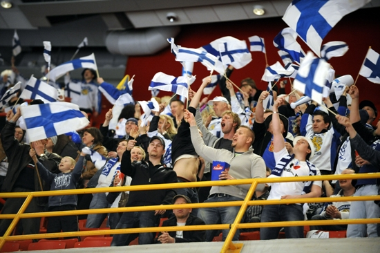A crowd waving Finnish flags.