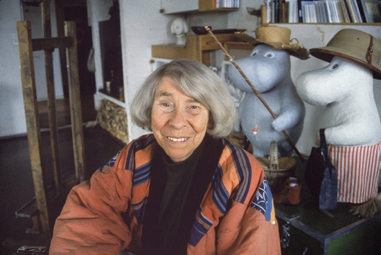 An elderly Tove Jansson pictured in front of two big Moomin plushies.