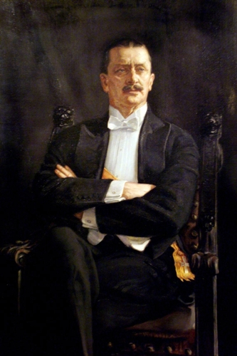 Painting of Mannerheim in a dark suit, sitting with his arms crossed.