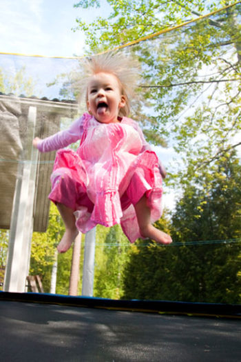 An excited-looking child in a pink dress jumping on a trampoline.