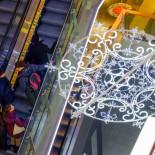 Um floco de neve gigante ilumina o shopping Citycenter (que fica do outro lado da Estação Ferroviária Central) enquanto clientes sobem a escada rolante.