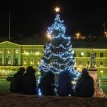 Do alto dos degraus da catedral na Praça do Senado, amigos admiram a árvore de Natal de 20 m de altura.