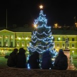 Un grupo de jóvenes contempla los 20 metros del Árbol de Navidad desde las escaleras de la Catedral Luterana, en la Plaza del Senado.