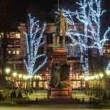 La statue du poète national finlandais Johann Ludvig Runeberg semble dominer du regard l'Esplanade d'Helsinki parée de ses plus beaux atours. En contrebas, on voit une statue de personnage féminin déroulant un manuscrit où figurent les paroles de l'hymne national finlandais écrites précisément par Runeberg : il s'agit là clairement d'une représentation allégorique de la Finlande.