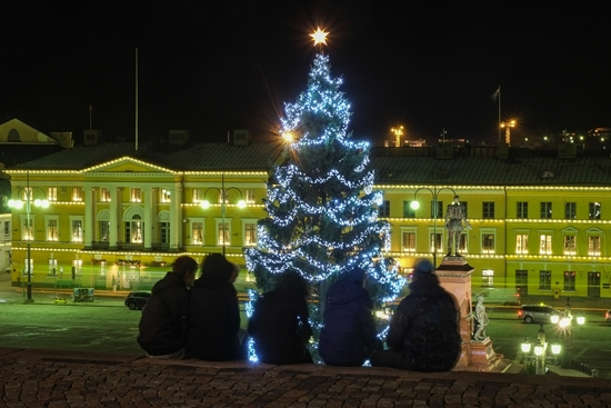 A group of friends admires the 20-metre (67-foot) Christmas tree from the cathedral steps on Senate Square.