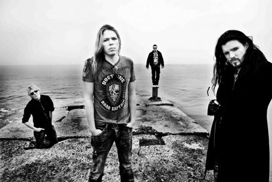 A black-and-white picture of the members of Apocalyptica standing on cliffs by water.