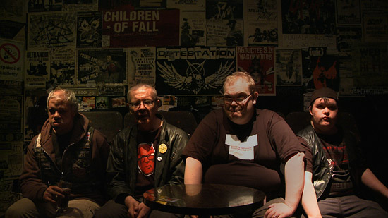 Members of Pertti Kurikan Nimipäivät sitting in a dimly -lit backstage room with walls covered with band posters.