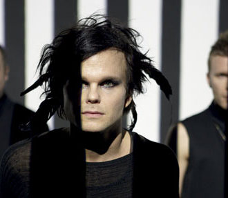 Lauri from The Rasmus with his signature black hair with feathers and dark eye makeup; the other band members in the background.