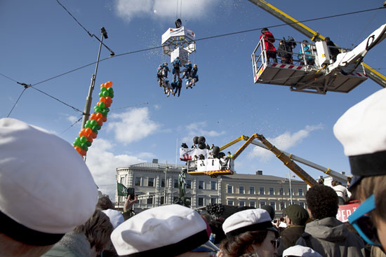 A group of university students being lift up by a crane; a group of other students watching.