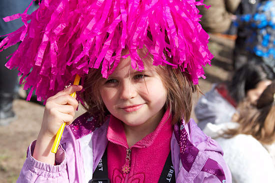 A young girl with a pink pompom.