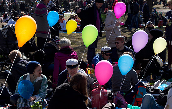 A large crowd of people picknicking at a park with colourful balloons.