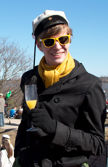 A smiling student in yellow sunglasses and scarf and the graduation cap holding a glass of Mimosa.