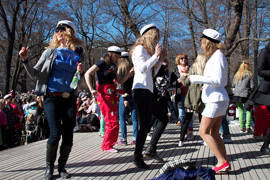 Students dancing outside on a wooden platform.