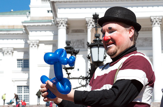 A smiling clown creating balloon figures in front of Helsinki Cathedral.