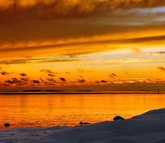 A winter sunset fills the sky and the sea with shades of orange on the island of Uunisaari at the southern end of Helsinki.