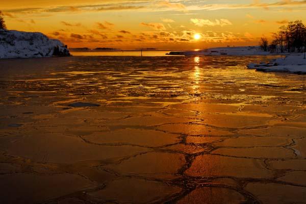 El sol se pone sobre el mar invernal a la espalda de Kaivopuisto, el parque que da forma al extremo sur de Helsinki.  Foto: Niklas Sjöblom/taivasalla.net