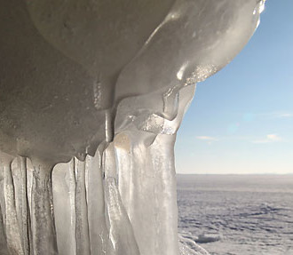 The sun helps the edge of an ice floe melt into a thicket of stalactites and stalagmites.