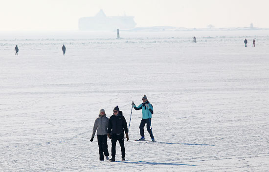 Ski the sea: Walkers share the ice with a skier blazing his own trail across the frozen seascape. Farther out, the shipping lanes are kept open, but it's safe to watch from a distance. Photo: Tim Bird