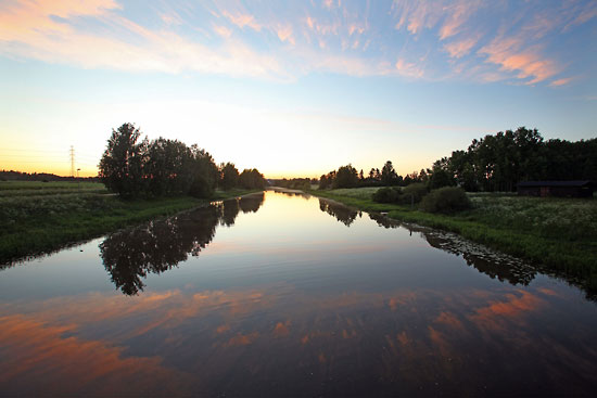 The slow descent of the sun on long summer evenings provides spectacular sunsets which are eerily reflected in the still waters of the Vantaa River. Photo: Tim Bird