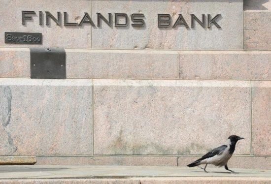 Le corbeau et la Banque de Finlande : cette photo fait référence à Klaus Waris, gouverneur de la Banque de Finlande entre 1957 et 1967, le nom Waris se prononçant varis, mot qui signifie justement corbeau en finnois. Wuolijoki s'est précipité pour saisir un corbeau passant devant la statue du banquier, rue Snellmaninkatu à Helsinki : « On dirait que l'oiseau vient de quitter son bureau en fin de journée. » Photo: Jukka Wuolijoki