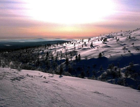 Le mont Pallas sous le soleil : « En regardant attentivement en haut à droite, on remarque le télésiège de la station de sports d'hiver avoisinante. Sur cette photo prise à la fin de l'hiver, la neige étincelle de tous ses feux sur le mont ; les sommets qu'on devine à l'arrière-plan sont quant à eux situés du côté suédois de la frontière lapone. » Photo: Jukka Wuolijoki