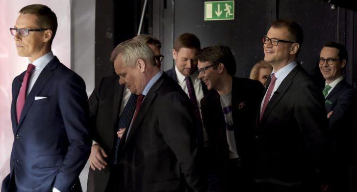 Grupo de líderes partidários finlandeses de oito partidos diferentes aguardam nos bastidores pelo holofotes da TV.