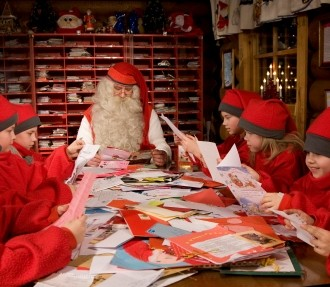 Santa Claus and some young elves sitting at a long table reading letters and cards from children.