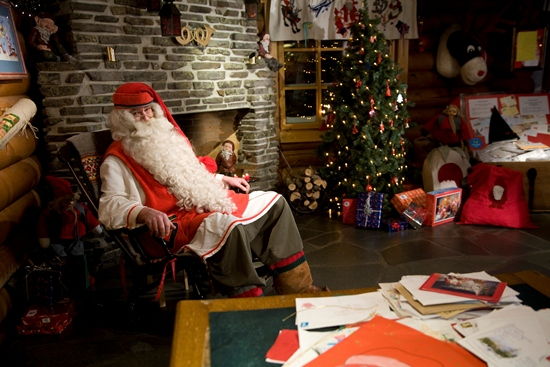 Santa Claus sitting in a rocking chair by a fireplace; a Christmas tree in the background.