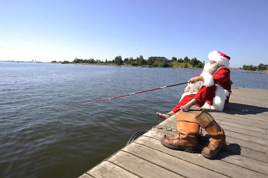 """Pescar es una de las aficiones de Papá Noel, aunque nunca pesque nada. Aquí lo vemos durante sus vacaciones del pasado junio en """"el sur"""", o sea, en Helsinki."""