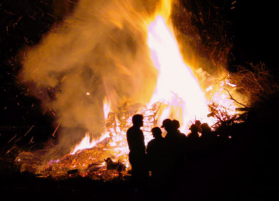 A huge bonfire; people seen as silhouettes in front of it.