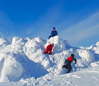 Three children climbing and playing in a huge pile of snow.