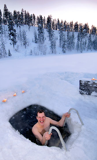 A widely smiling man dipping in a hole in the ice.
