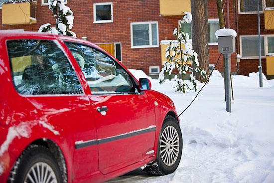 A red car attached to an engine-block heater.