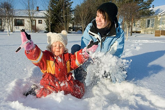 A small child dressed in coveralls sitting in the snow, throwing the snow upwards; an older person next to the child.