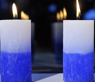 Two blue-and-white candles burning on a window sill.