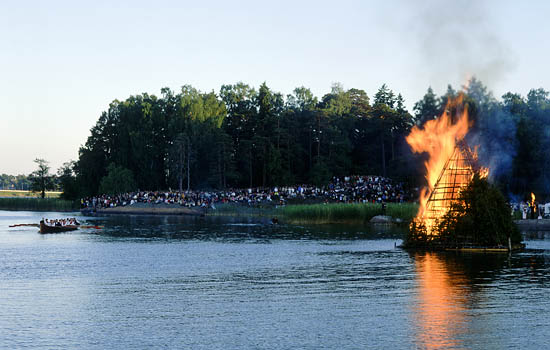 A crowd gathered to watch a large bonfire by water.