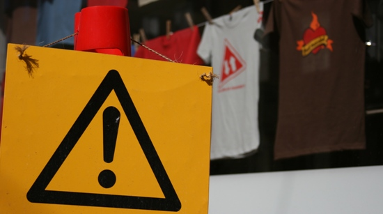 Coincidence? A sign urges caution during roadwork outside the shop, but also draws attention to the T-shirts within.