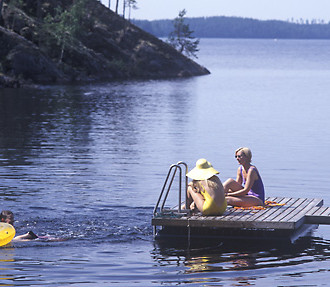 A perfect summer day on a Finnish lake: sitting on a pier while kids are splashing in the water.