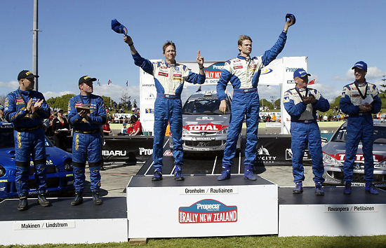 Finnish drivers took the first three places at the Rally of New Zealand in October 2002. At centre-left is winner and World Champion Marcus Grönholm with co-driver Timo Rautiainen. On their left are Harri Rovanperä and co-driver Risto Pietiläinen, and on their right third-placed Tommi Mäkinen with co-driver Kaj Lindström.