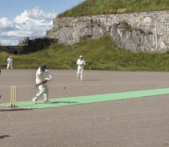 This match is taking place in distinguished surroundings on the island fortress of Suomenlinna just outside Helsinki. To provide a better surface for bowling and batting, a nylon mat is laid over the gravel surface.