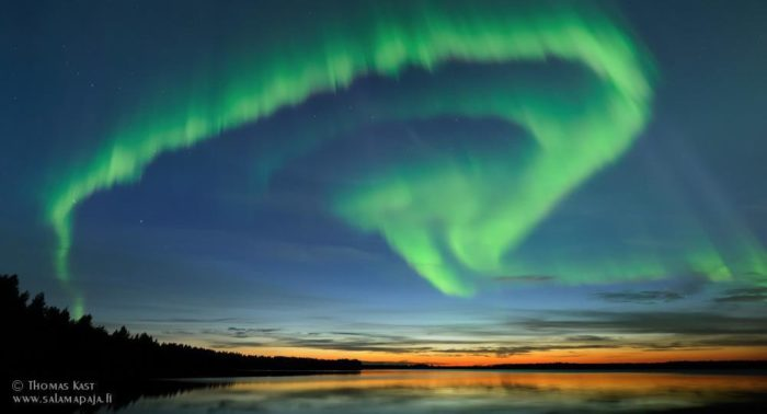 Green, spiral-shaped aurora borealis over a lake.