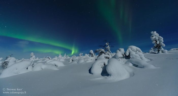 Aurora borealis in the dark sky over a snowy landscape.