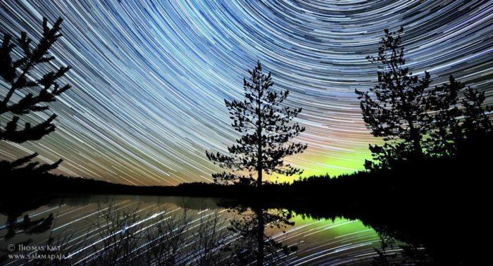 Kast zeigt die Bewegung des nächtlichen Sternenhimmels, indem er eine Sequenz von 200 Fotos zu einem einzigen Foto verbindet. Dadurch werden am Horizont die grünen, gelben und orangfarbenen Nordlichter sichtbar.