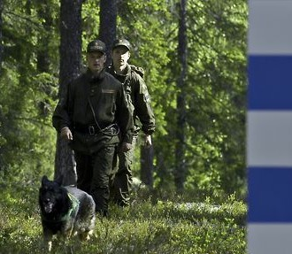 Two Finnish border guards walking by the border with a dog.
