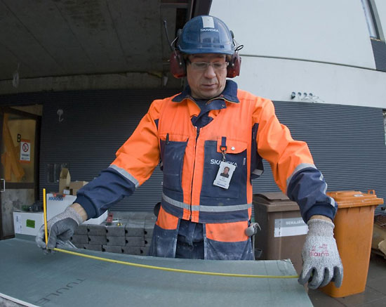 A construction worker measuring a piece of material.