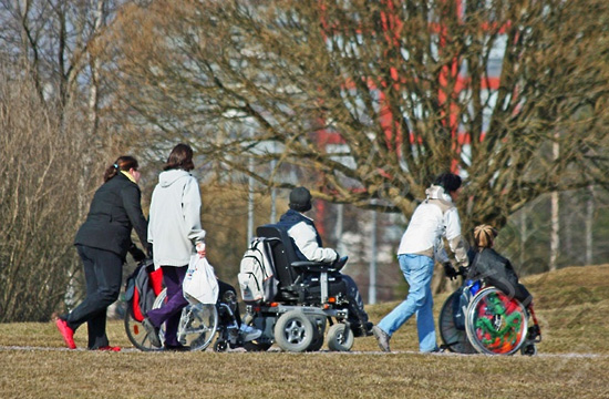 Three people pushing three other people in wheelchairs outside in a park.