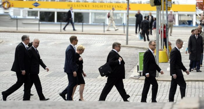 Die neuen Kabinettsmitglieder laufen auf ihrem Weg zu einer Pressekonferenz am gelben Helsinki-Sightseeing-Schiff vorbei.