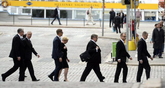 Члены нового кабинета министров направляются на пресс-конференцию, на фоне виден желтый прогулочный катер, совершающий экскурсионные туры вдоль берегов Хельсинки.