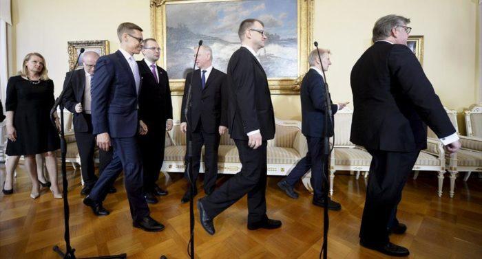 Eine Ansammlung von 14 soeben vereidigten Ministern versucht sich, für ein Gruppenfoto zu ordnen und zu lächeln.