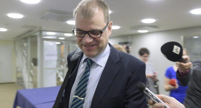 Tout en s'autorisant un sourire, le Premier ministre Juha Sipilä élude les questions de quelques journalistes.